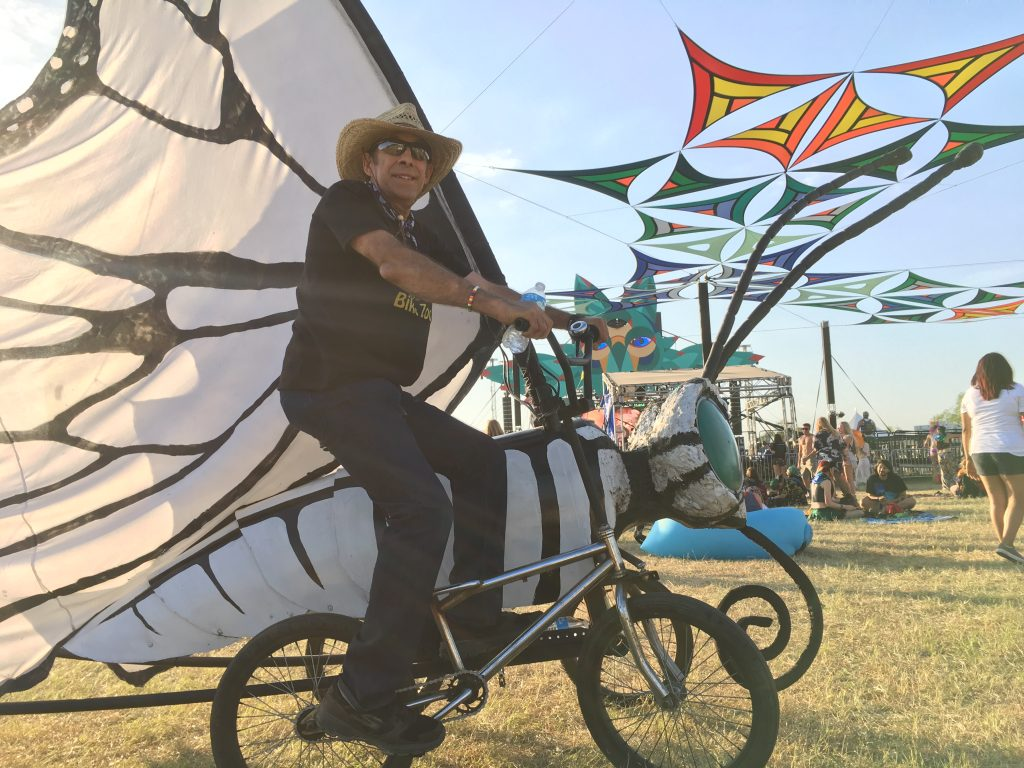 Grant Schaubhut, owner of the Austin Bike Zoo, riding around the festival grounds on one of his homemade butterfly bicycles.