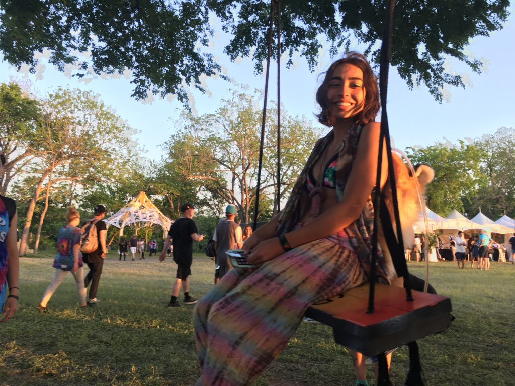 Aleah Doody, a 21-year-old sophomore from Trinity University enjoys chilling out on a swing hanging from the Tree of Life at Euphoria.