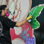 "J Muzacz mentors Caminos ""caminantes,"" Latinx teenagers from 15 to 18 years of age that are interested in creative arts. The Caminos program offers them a paid internship to develop that interest. One of his charges, Adrian Muniz, asked him for help facilitate live painting during the MACC Día De Los Muertos event. A passerby noted their use of brushes, but Muzacz tells his students, ""You don't have to be all spray. Use whatever gets the job done."""