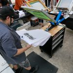 Joseph Piedra works on printing shirts for the Día De Los Muertos event at the MACC. Piedra estimated that he printed 50 shirts in one hour of being at the event. His wife owns an online screen printing business, Old School Nation, which incorporated live screen printing during the past two years.