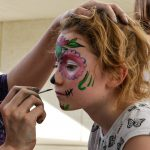 Bella Mae, one of the many children at the Día De Los Muertos event, patiently gets her face painted.