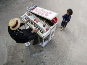 "Adam Lozoya, ""The Traveling Pianist,"" plays for a young fan at Canopy, an arts complex housed in an old warehouse in East Austin."