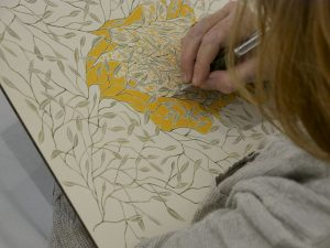 Trish Sierer, an artist at Art.Science.Gallery, uses an X-Acto knife to carve into clay covering a piece of cardboard.