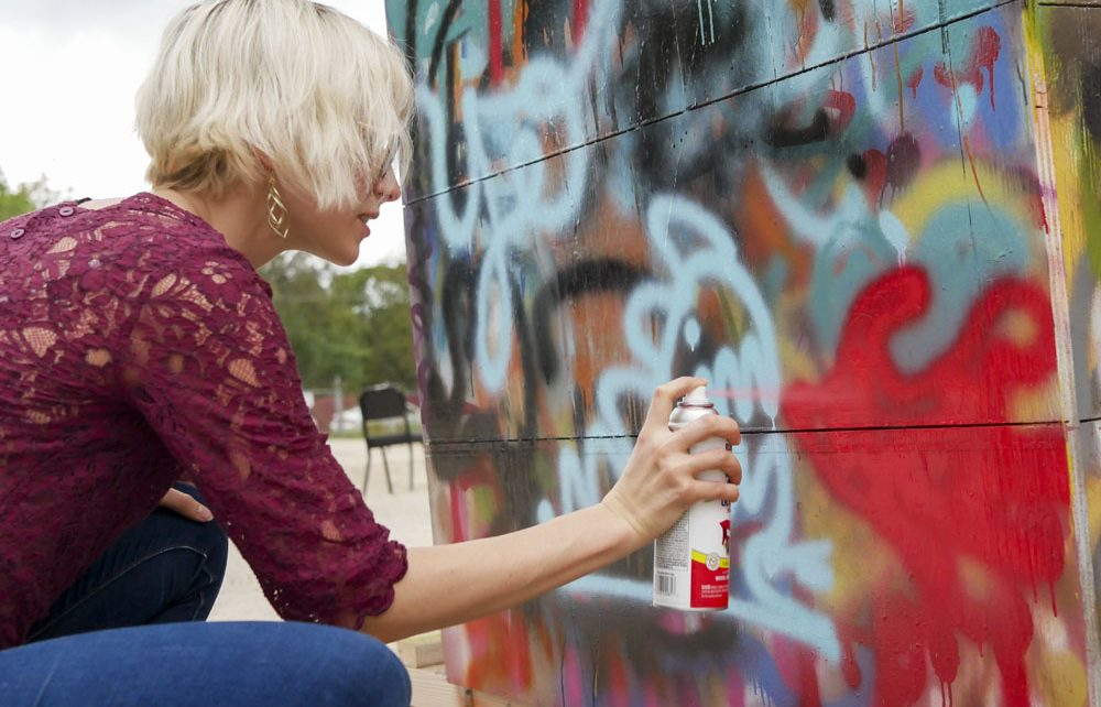 Chanel Rector spray paints a public wall in the parking lot of Canopy while her friends waited out of view.