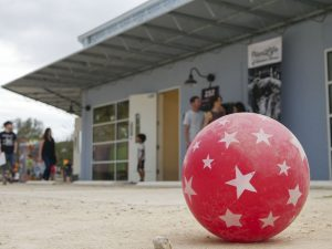 A red ball covered in white stars and dust from the parking lot at Canopy sits still after children tired of playing with it during EAST activities at Canopy. In the background, attendees walk from gallery to gallery under a gray sky.