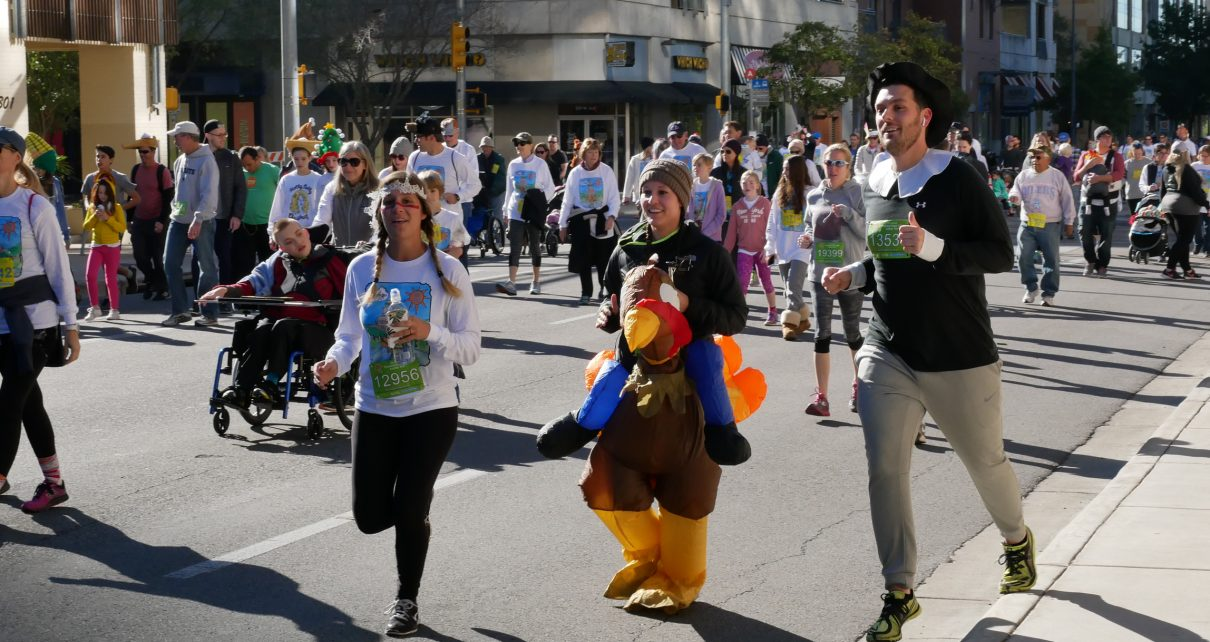 Three runners wear Thanksgiving costumes during the untimed portion of the Turkey Trot.